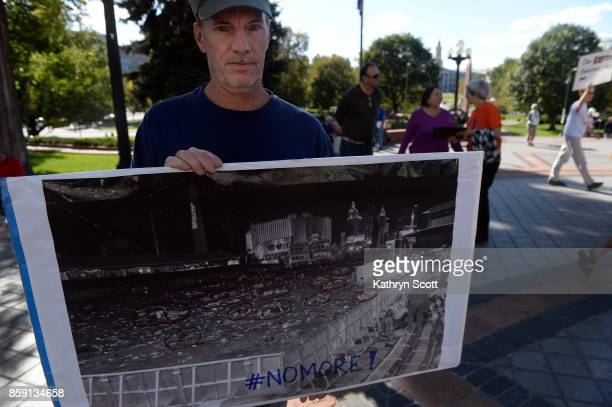 Christopher Savin holds a poster with a photo from last week's mass shooting in Las Vegas as he stands with a small crowd on the west steps of the...