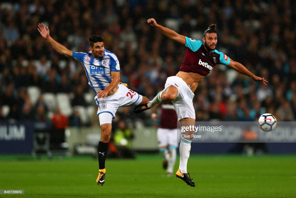 Christopher Schindler of Huddersfield Town and Andy Carroll of West Ham United jump for the ball during the Premier League match between West Ham United and Huddersfield Town at London Stadium on September 11, 2017 in London, England.