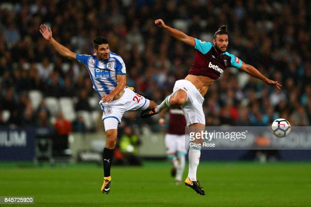 Christopher Schindler of Huddersfield Town and Andy Carroll of West Ham United jump for the ball during the Premier League match between West Ham...