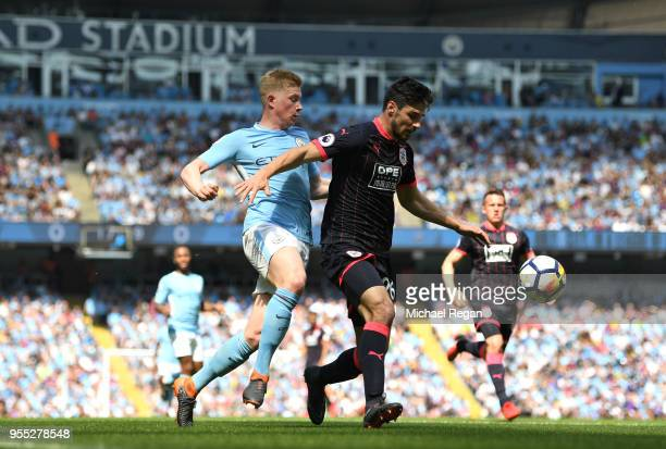 Christopher Schindler of Huddersfield Town is challenged by Kevin De Bruyne of Manchester City during the Premier League match between Manchester...