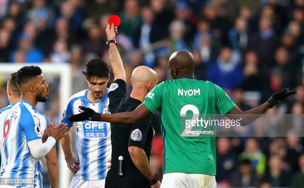 Christopher Schindler of Huddersfield Town is shown a red card by referee Roger East during the Premier League match between Huddersfield Town and...