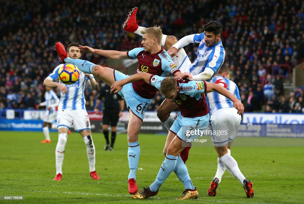 Christopher Schindler of Huddersfield Town tangles with Ben Mee and Charlie Taylor of Burnley during the Premier League match between Huddersfield Town and Burnley at John Smith's Stadium on December 30, 2017 in Huddersfield, England.