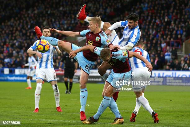 Christopher Schindler of Huddersfield Town tangles with Ben Mee and Charlie Taylor of Burnley during the Premier League match between Huddersfield...