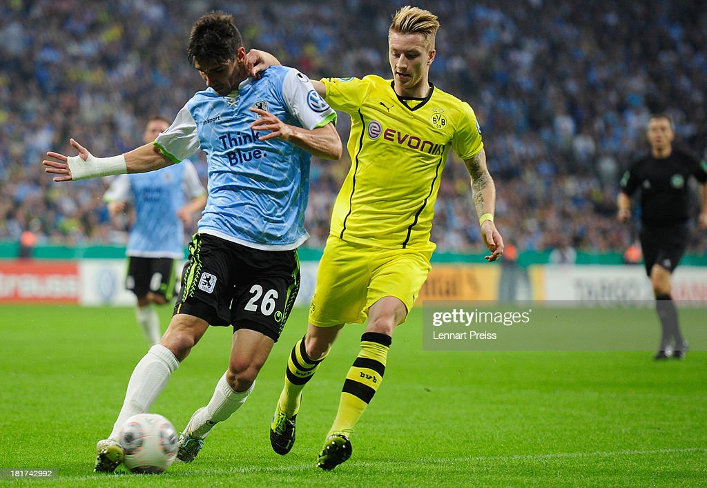 Christopher Schindler (L) of Muenchen challenges Marco Reus of Dortmund during the DFB Cup match between TSV 1860 Muenchen and Borussia Dortmund at Allianz Arena on September 24, 2013 in Munich, Germany.
