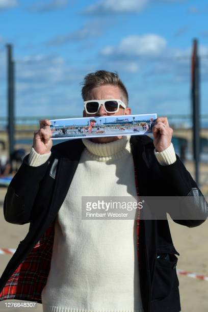 Christopher Spencer, aka: Cold War Steve poses with a picture of the censored artwork on Boscombe beach on September 25, 2020 in Bournemouth,...