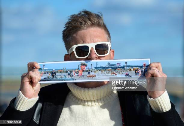 Christopher Spencer aka Cold War Steve poses with a picture of the censored artwork on Boscombe beach on September 25 2020 in Bournemouth England The...