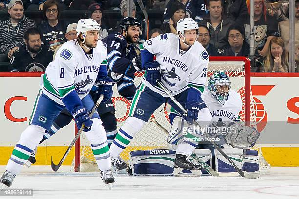 Christopher Tanev Alexander Edler goaltender Ryan Miller of the Vancouver Canucks and Anthony Peluso of the Winnipeg Jets keep an eye on the play...