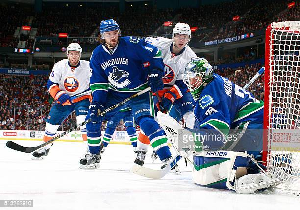 Christopher Tanev of the Vancouver Canucks and Shane Prince of the New York Islanders watch Jacob Markstrom of the Canucks make a glove save during...