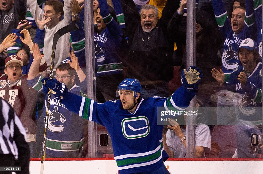 Christopher Tanev #8 of the Vancouver Canucks celebrates after scoring the game winning goal against the Calgary Flames in overtime in NHL action in Vancouver, BC, on December, 20, 2014 at Rogers Arena in Vancouver, British Columbia, Canada.