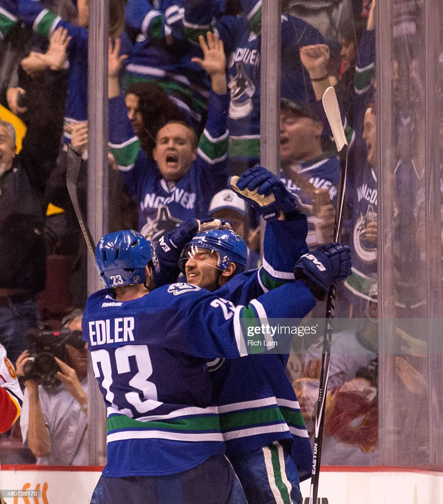 Christopher Tanev #8 of the Vancouver Canucks celebrates with Alexander Edler #23 after scoring the game winning goal against the Calgary Flames in overtime in NHL action in Vancouver, BC, on December, 20, 2014 at Rogers Arena in Vancouver, British Columbia, Canada.