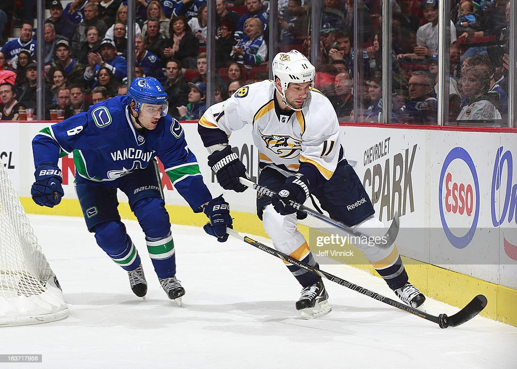 Christopher Tanev #8 of the Vancouver Canucks checks the puck off the stick of David Legwand #11 of the Nashville Predators during an NHL game at Rogers Arena March 14, 2013 in Vancouver, British Columbia, Canada. Vancouver won 7-4.