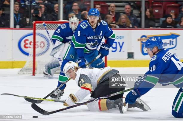 Christopher Tanev of the Vancouver Canucks looks on as teammate Elias Pettersson checks Cody Eakin of the Vegas Golden Knights during their NHL game...