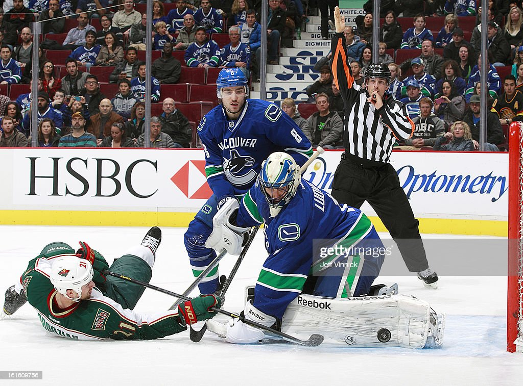 Christopher Tanev #8 of the Vancouver Canucks watches Roberto Luongo #1 of the Canucks make a save on Kyle Brodziak #21 of the Minnesota Wild during their NHL game at Rogers Arena February 12, 2013 in Vancouver, British Columbia, Canada. Vancouver won 2-1