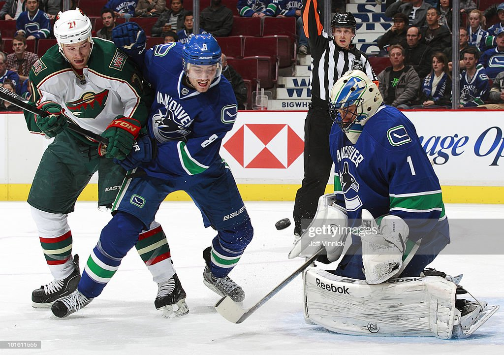 Christopher Tanev #8 of the Vancouver Canucks watches Roberto Luongo #1 of the Canucks make a save off the shot of Kyle Brodziak #21 of the Minnesota Wild during their NHL game at Rogers Arena February 12, 2013 in Vancouver, British Columbia, Canada. Vancouver won 2-1