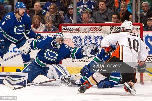Christopher Tanev watches Ryan Miller of the Vancouver Canucks make a save on Corey Perry of the Anaheim Ducks during their NHL game at Rogers Arena...