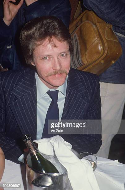 Christopher Walken smiling at camera while sitting at his table at an event circa 1970 New York