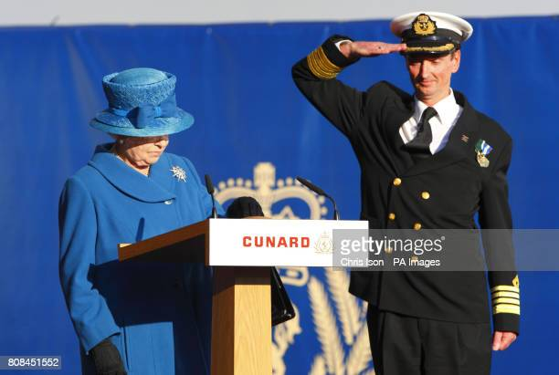 Christopher Wells Captain of the Queen Elizabeth salutes as Her Majesty Queen Elizabeth II presses a button to release the bottle of white wine to...