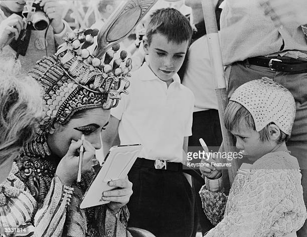Christopher Wilding looks on as his mother American actress Elizabeth Taylor makes up her eyes for her role as Cleopatra in Joseph L Mankiewicz's...