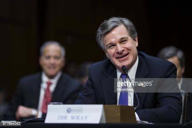 Christopher Wray director of the Federal Bureau of Investigation smiles while testifying during a Senate Intelligence Committee hearing on worldwide...