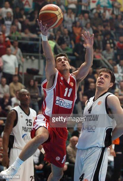 Christos Harissis of Olympiacos Piraeus controls the ball in front of Partizan Belgrade's Milenko Tepic during their basketball Euroleague Top 16...
