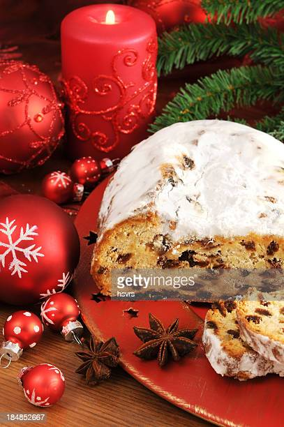 christstollen on red plate with Christmas Ornament and Candle