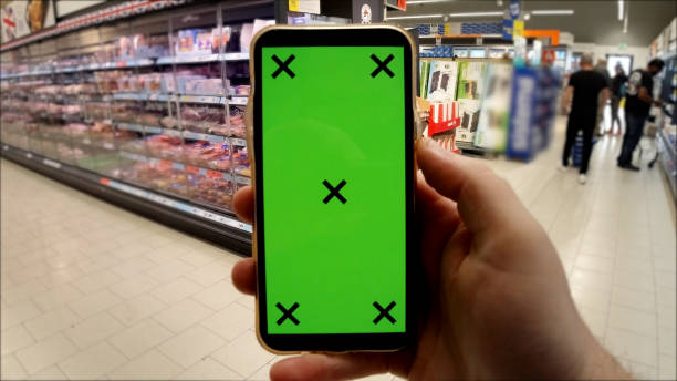 Chroma Key Green screen of phone in Fresh whole food produce supermarket retail space. Typical shopping mall retail space. London, UK