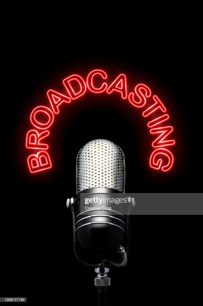 A chrome microphone underneath a red neon broadcasting sign : Stock Photo