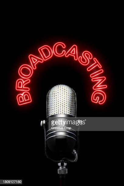 a chrome microphone underneath a red neon broadcasting sign - microzoa stock pictures, royalty-free photos & images