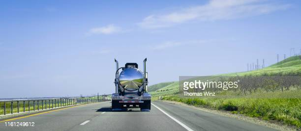 chrome tanker truck on the freeway - rear view stock pictures, royalty-free photos & images