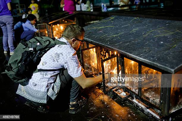 A chruch goer places a candle during Christmas eve mass at Ganjuran church on December 24 2013 in Yogyakarta Indonesia Christmas is a national...