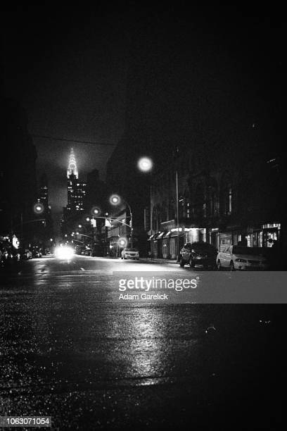 chrysler building in distance at night - film noir style stock photos and pictures