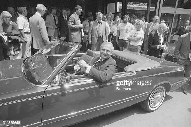 Chrysler Chairman Lee Iacocca sits in the front seat of a 1982 1/2 prototype Chrysler LeBaron Convertible while curious onlookers examine the new car...