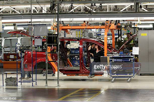 A Chrysler Group LLC employee inspects the frame of a Chrysler minivan as it moves down the production line at Chrysler Group's assembly plant in...