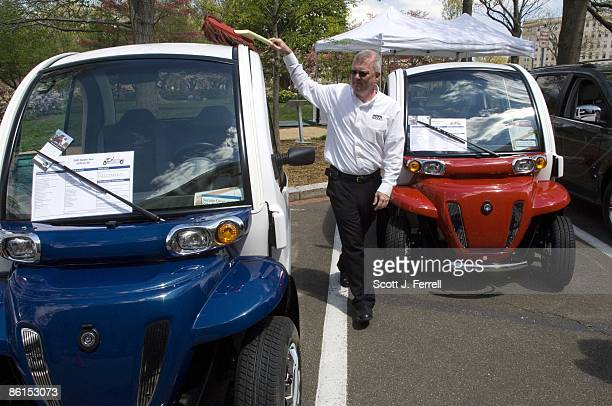 Chrysler product engineering executive Douglas J Quigley dusts pollen off Global Electric Motorcars models GEM eL left and the GEM e4 which were part...