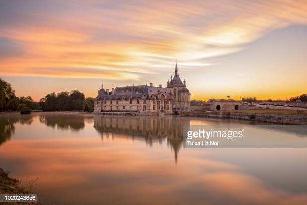 château de chantilly bathing in early sun light - oise stock photos and pictures