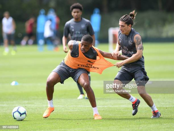 Chuba Akpom and Hector Bellerin of Arsenal fight for the ball during a training session at London Colney on July 4 2018 in St Albans England