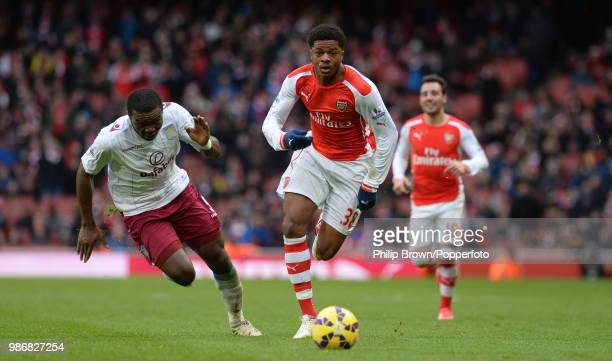 Chuba Akpom of Arsenal and Jores Okore of Aston Villa chase after the ball during the Barclays Premier League match between Arsenal and Aston Villa...