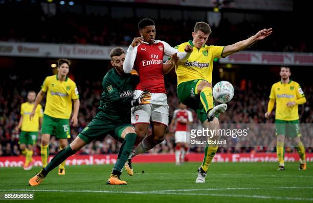 Chuba Akpom of Arsenal is challenged by Christoph Zimmermann of Norwich City and Angus Gunn of Norwich City during the Carabao Cup Fourth Round match...