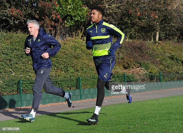 Chuba Akpom of Arsenal running with Arsenal Fitness Coach Craig Gant during the Arsenal Training Session at London Colney on December 5 2016 in St...