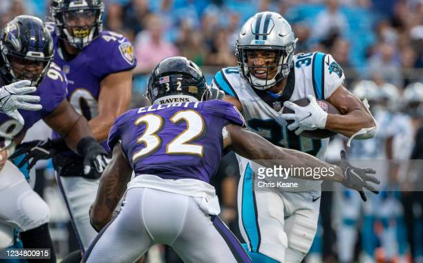 Chuba Hubbard of the Carolina Panthers runs the ball against DeShon Elliott of the Baltimore Ravens during the first half of a NFL preseason game at...