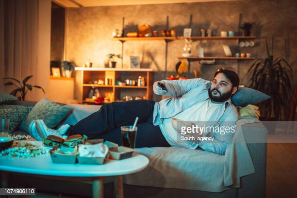 chubby guy changing channels - couch potato stock pictures, royalty-free photos & images