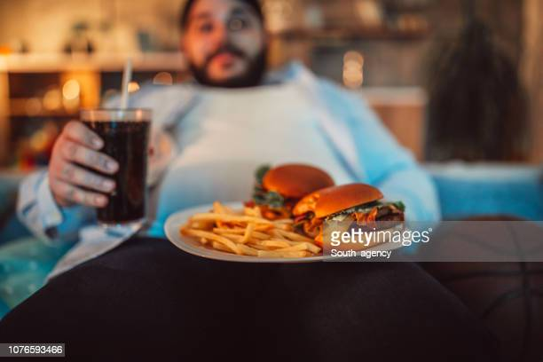 chubby guy eating junk food - unhealthy living stock pictures, royalty-free photos & images