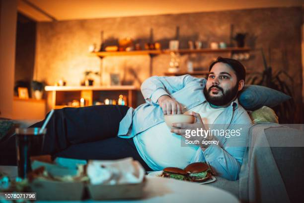 chubby guy eating on sofa - night in stock pictures, royalty-free photos & images