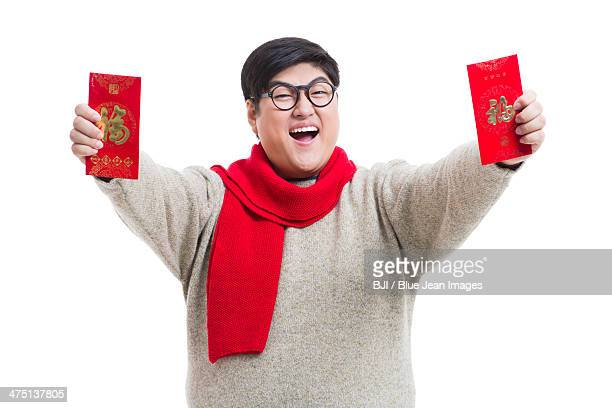 Chubby young man with red packets celebrating Chinese New Year