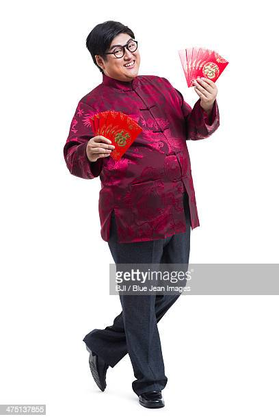 chubby young man with red packets celebrating chinese new year - só homens jovens imagens e fotografias de stock