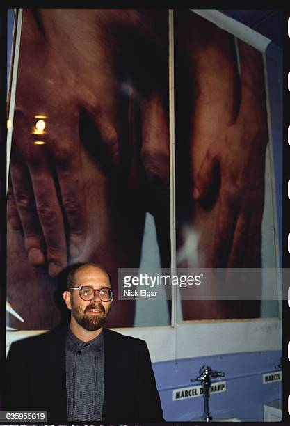 Chuck Close with his photograph display in the men's restroom at Area a Manhattan nightclub