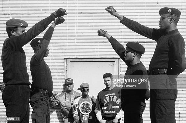 Chuck D Flavor Flav and Terminator X of hip hop group Public Enemy look through a guard of black power salutes in New York City on September 14 1988