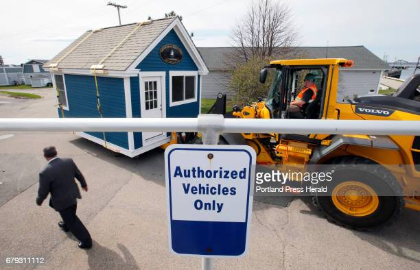 Chuck Gregory academic dean of Southern Maine Community College left walks past a shed being moved by Howie Hall driver of the frontend loader Plans...