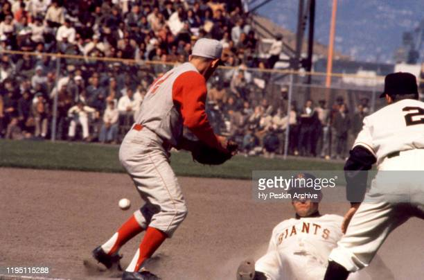 Chuck Hiller of the San Francisco Giants slides into third base after following his coach Salty Parker's instructions to slide as Gene Freese of the...