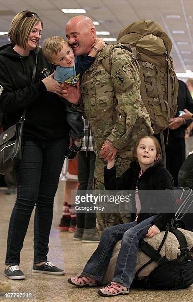 SSG Chuck Hoffman greets his wife Mundy kids Wade and Mikaela as members of the Utah National Guard's 19th Special Forces Airborne unit return from...